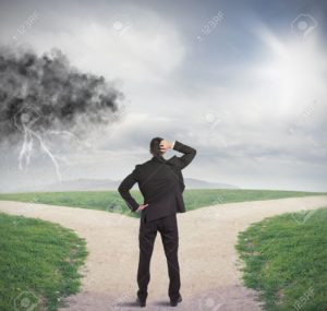 21393275-Businessman-at-a-crossroads-with-storm-and-sunshine-Stock-Photo